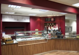 Bespoke counter with laminated worktop and wood effect laminate frontage, bulkhead above finished in company maroon emulsion paint