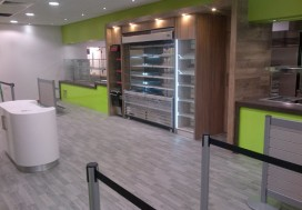 Bespoke counters with silestone worktops including drop to floor sections, frontage finished in green acrylic, central retail section finished in wood effect laminate with LED strip lighting on retail housing, grey wood effect vinyl flooring