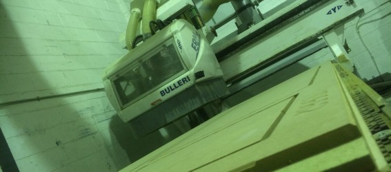 CNC routing machine with routered boards on bed